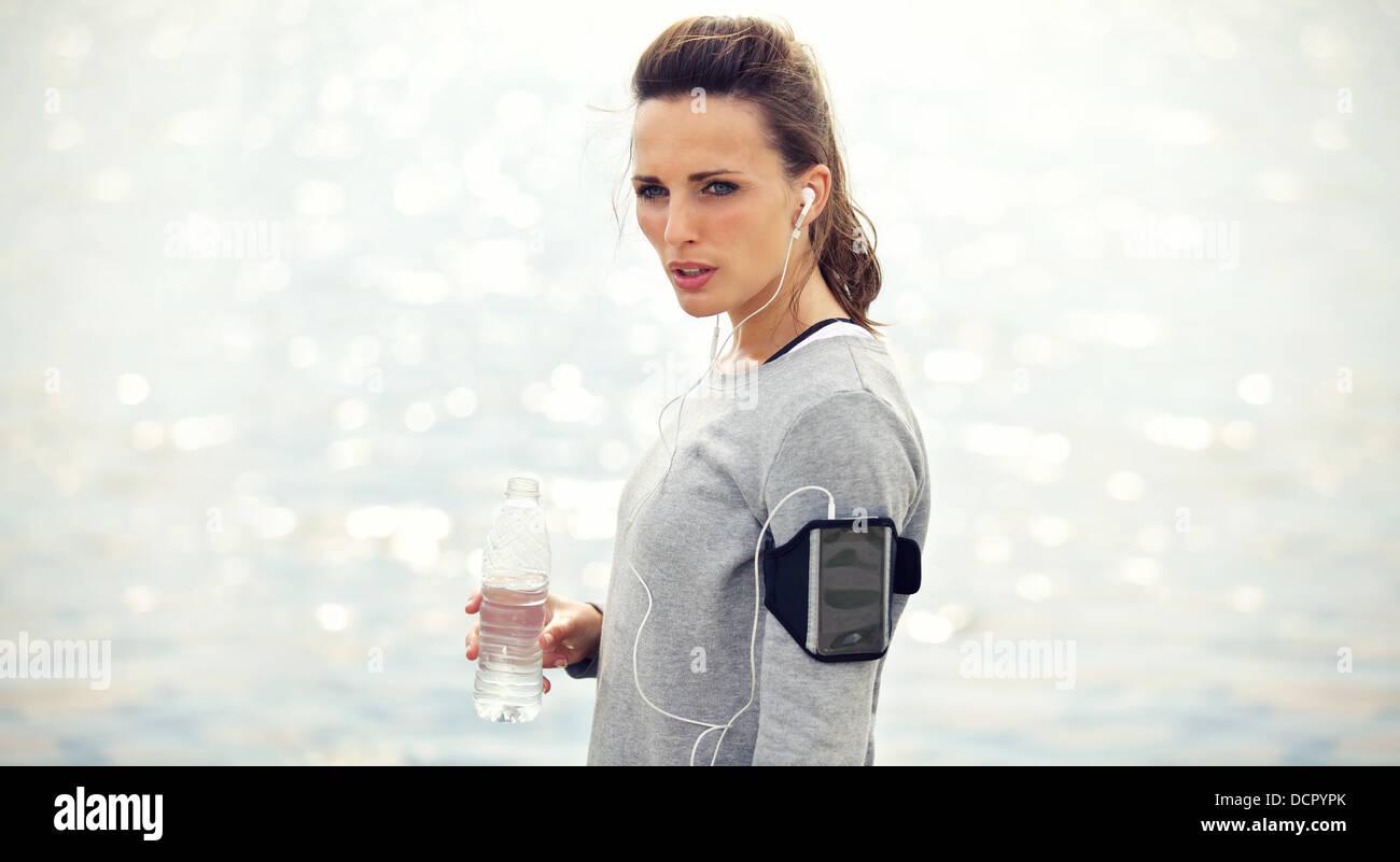 Female runner with bottled water tired from running - Stock Image