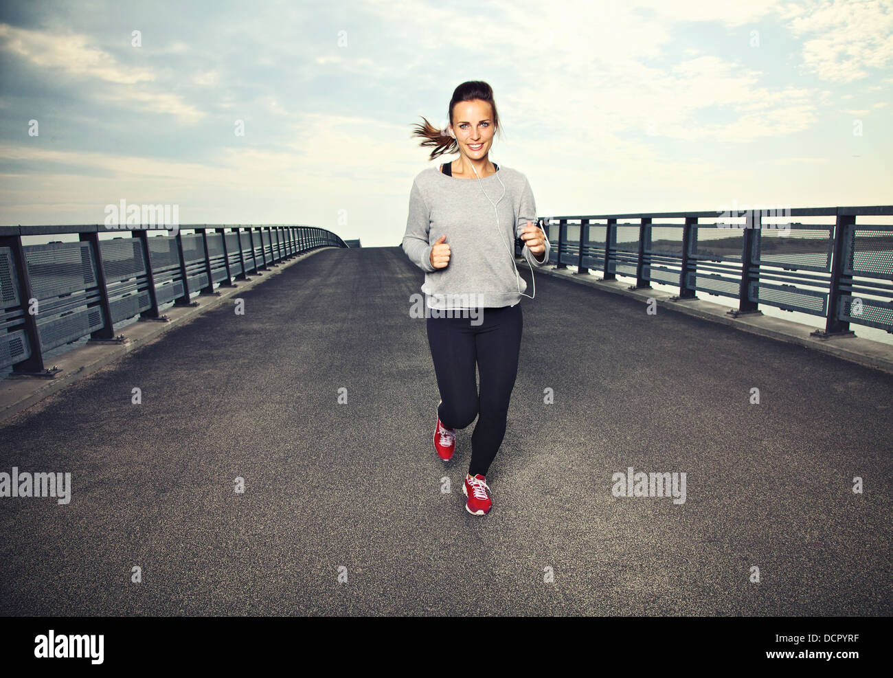 Smiling female runner doing running exercise - Stock Image