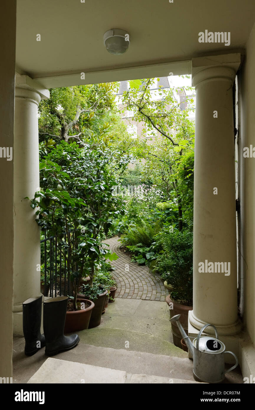 Portico with stone columns, watering can and wellington boots leading out to overgrown garden - Stock Image