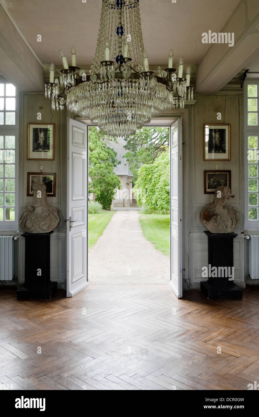 18C chandelier in entrance hall with parquet flooring and stone busts - Stock Image