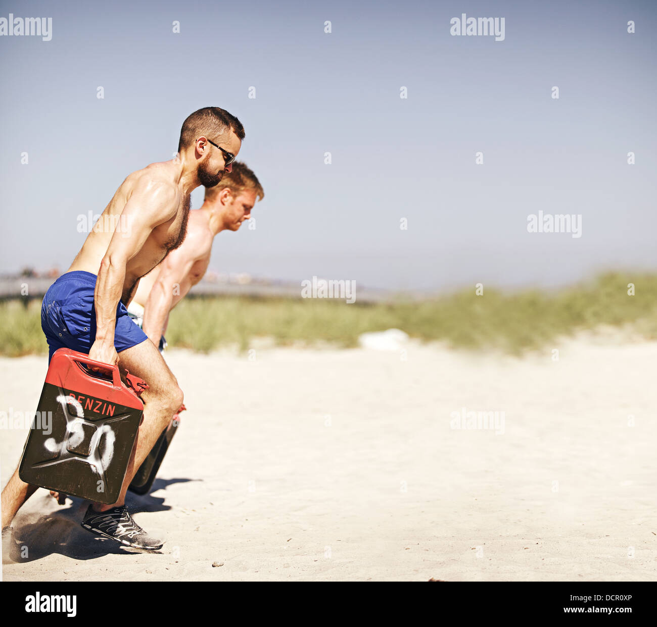 Men lifting heavy jerrycans during a crossfit workout on the beach - Stock Image