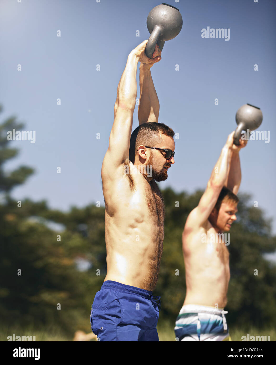 Two strong young men lifting heavy kettlebell weights - Stock Image