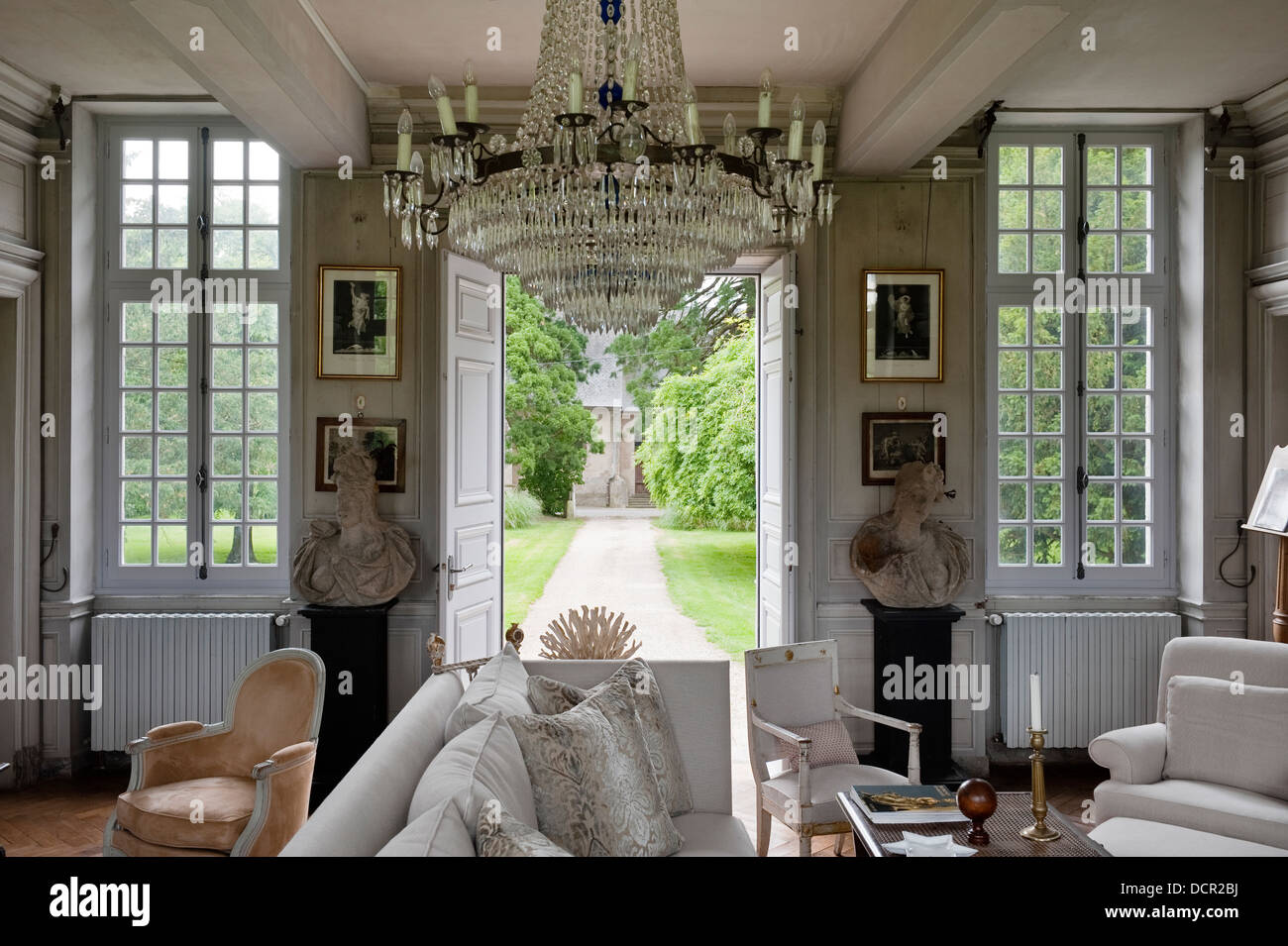 18C chandelier in sitting room furnished with French antiques, stone busts and with french doors leading out to - Stock Image