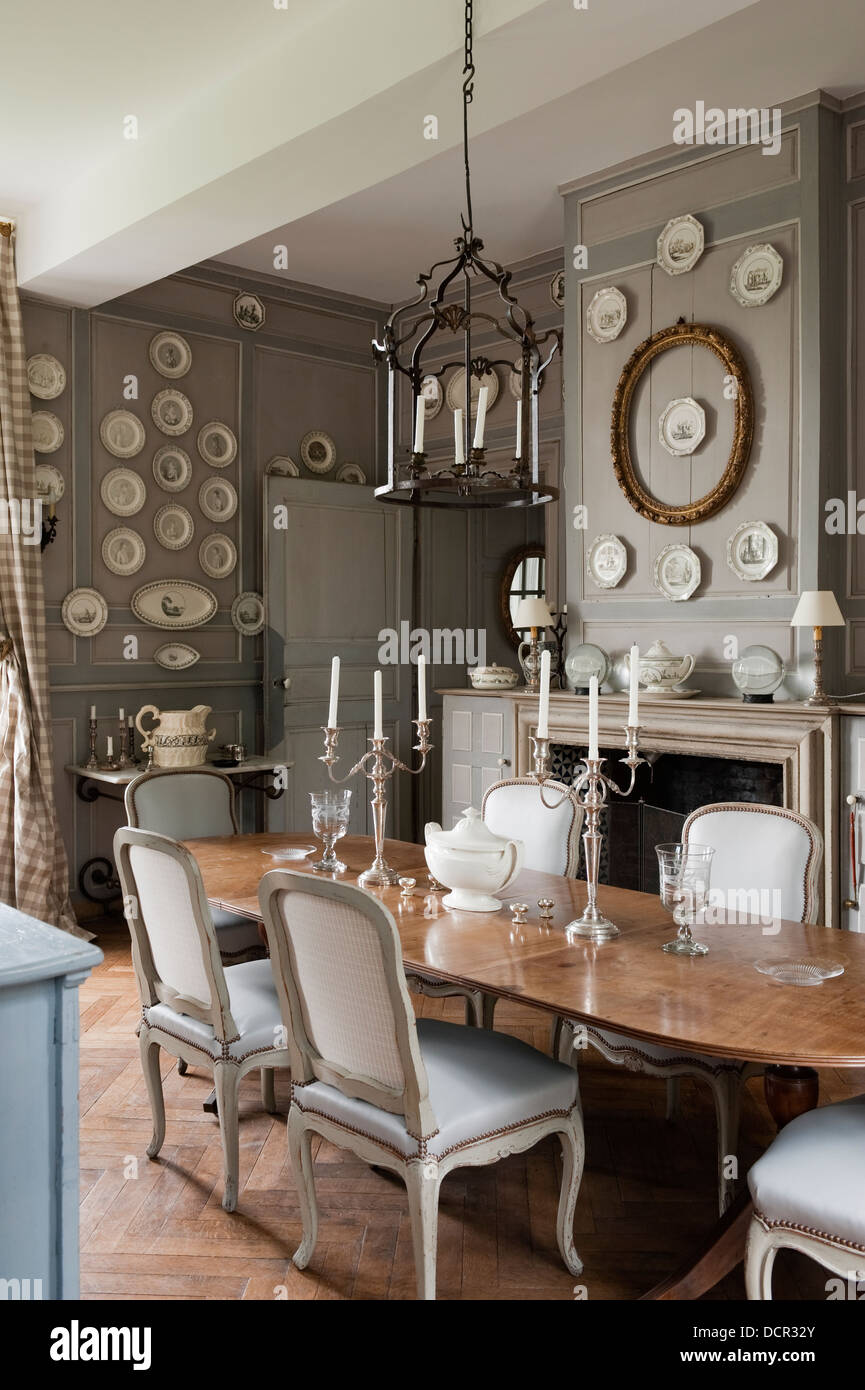 French Antique Chairs And Table In Elegant Dining Room With Wood Wall Paneling Decorative China Plates