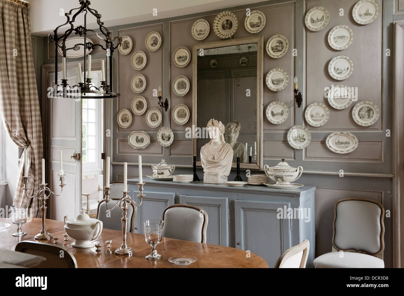 French Antique Chairs And Table In Elegant Dining Room With Wood Wall  Paneling And Decorative China Plates