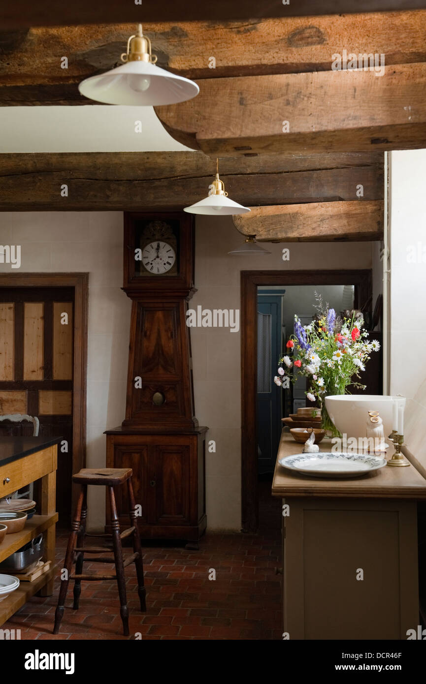 kitchen with wooden ceiling beams and an old grandfather clock - Stock Image