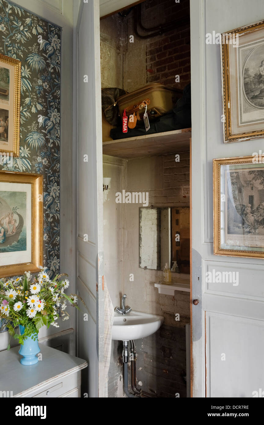 Bathroom concealed behind wood paneling in room with Marvic fabric lined walls - Stock Image