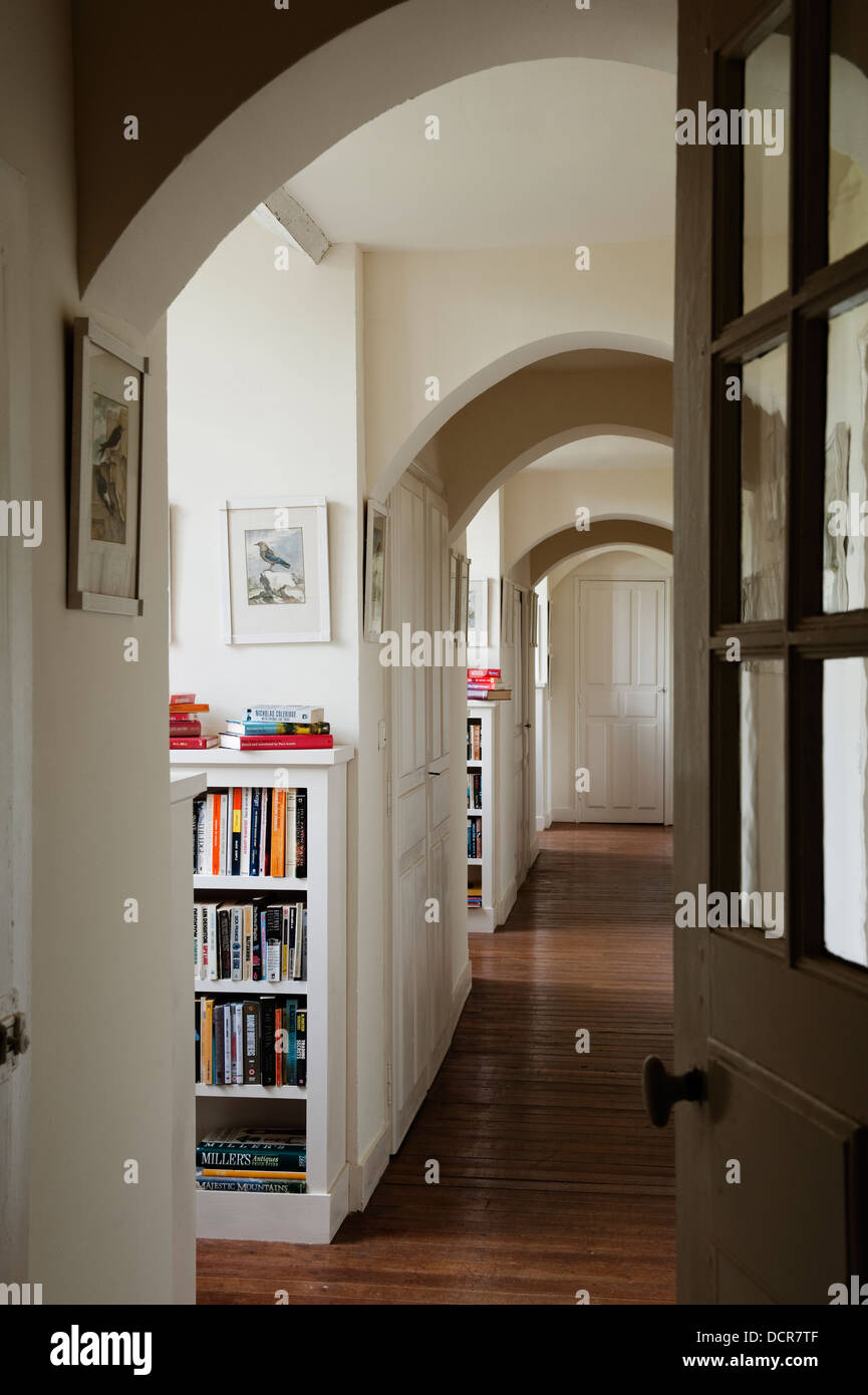 View down arched corridor with wooden flooring - Stock Image