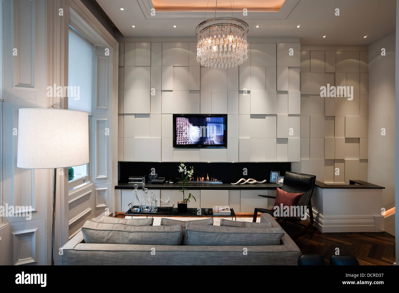 Seating area with glass chandelier and recessed fire in London city apartment - Stock Image