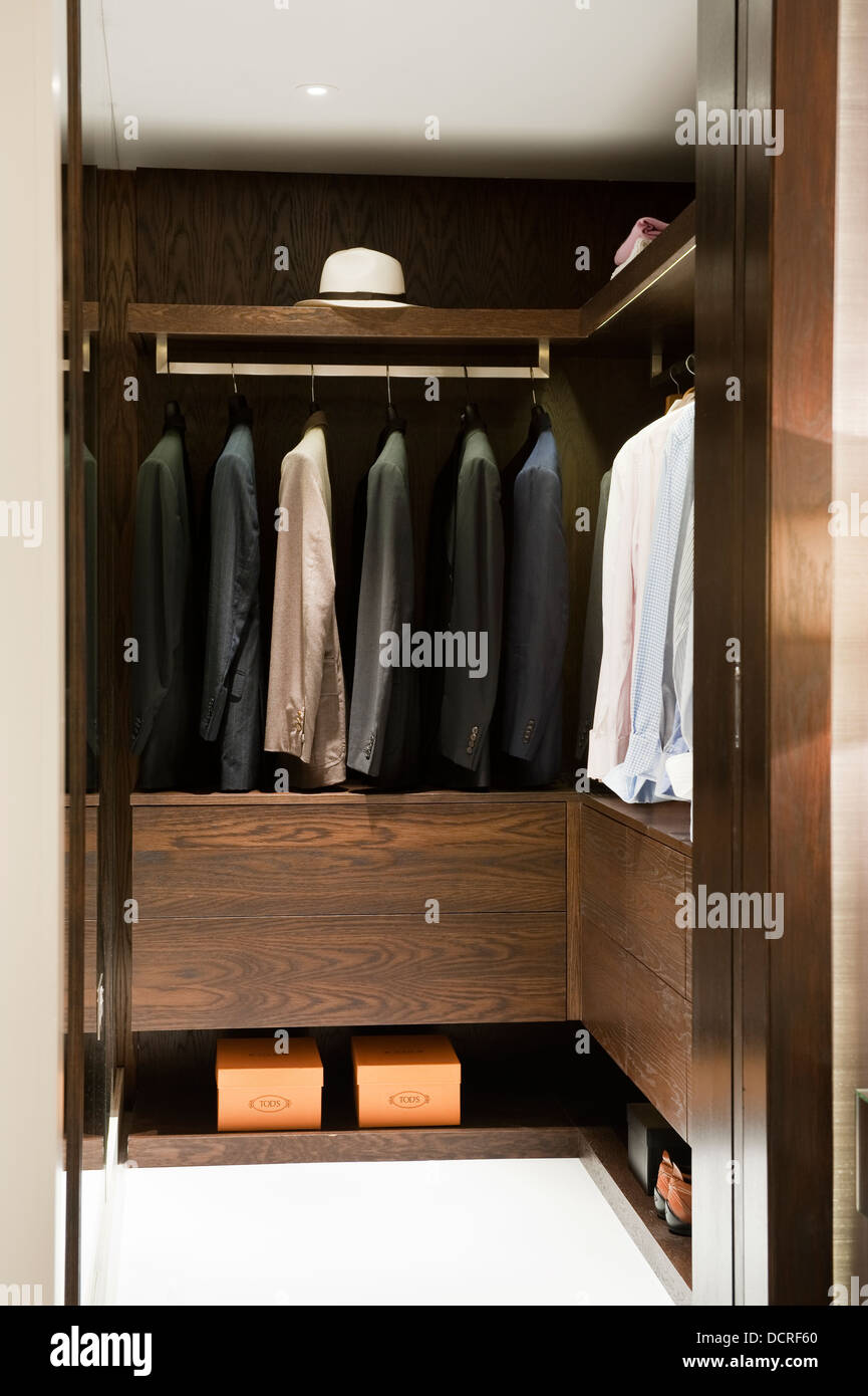 Jackets hang in dressing room of London city apartment Stock Photo