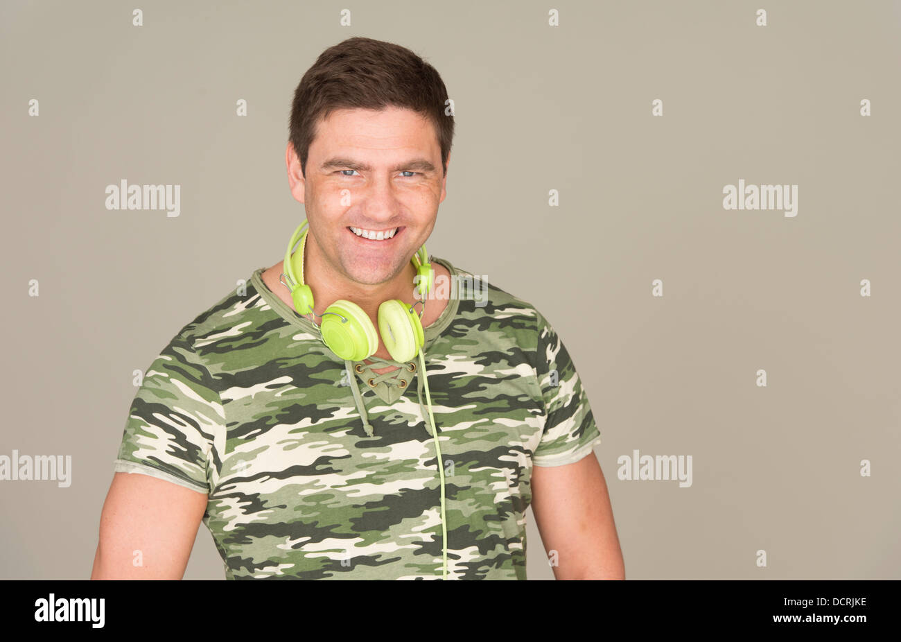Man with camouflage t-shirt and green headphones smiling at camera - Stock Image
