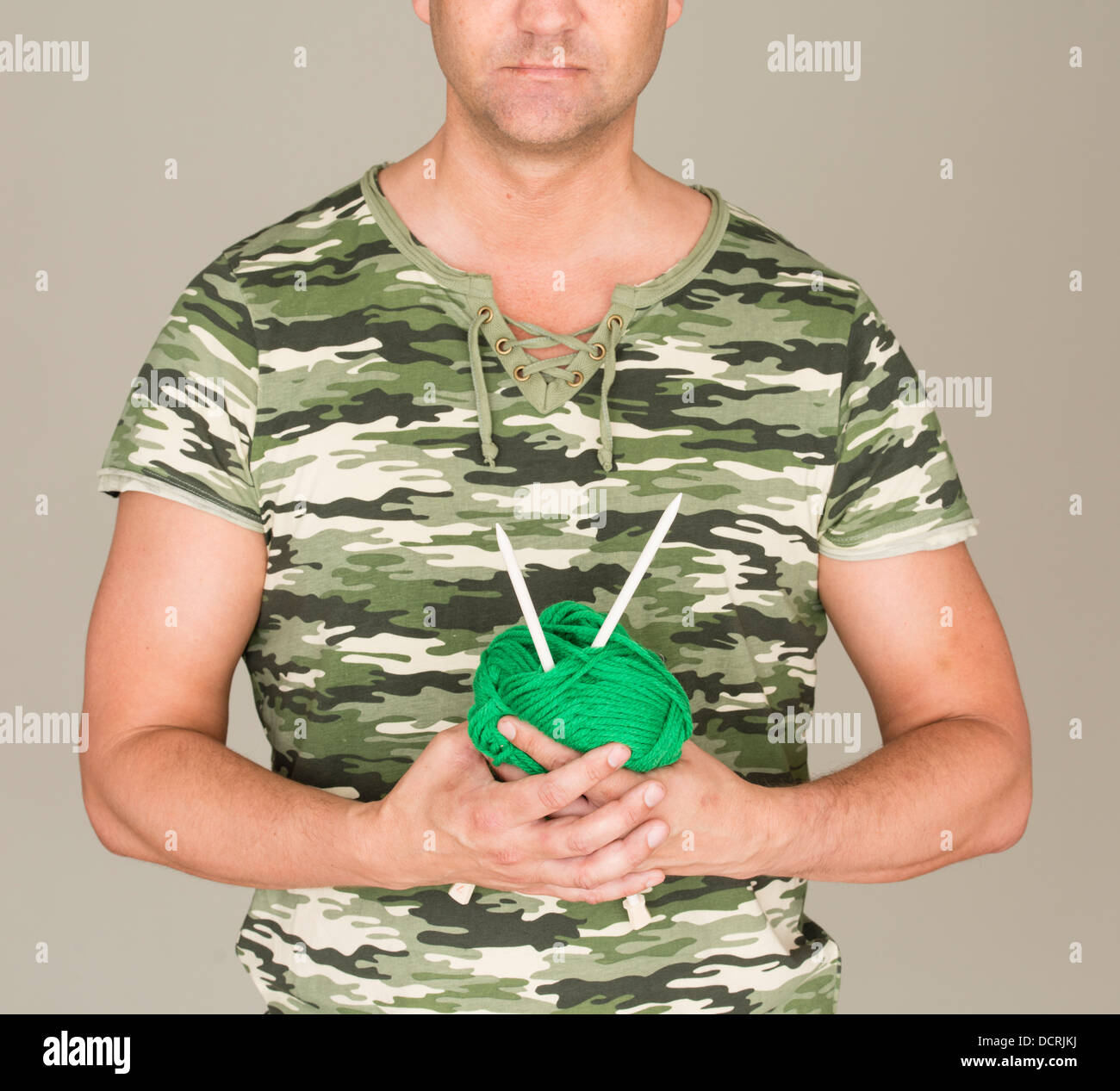 Man with camouflage t-shirt looking puzzled at a ball of yarn and knitting needles - Stock Image