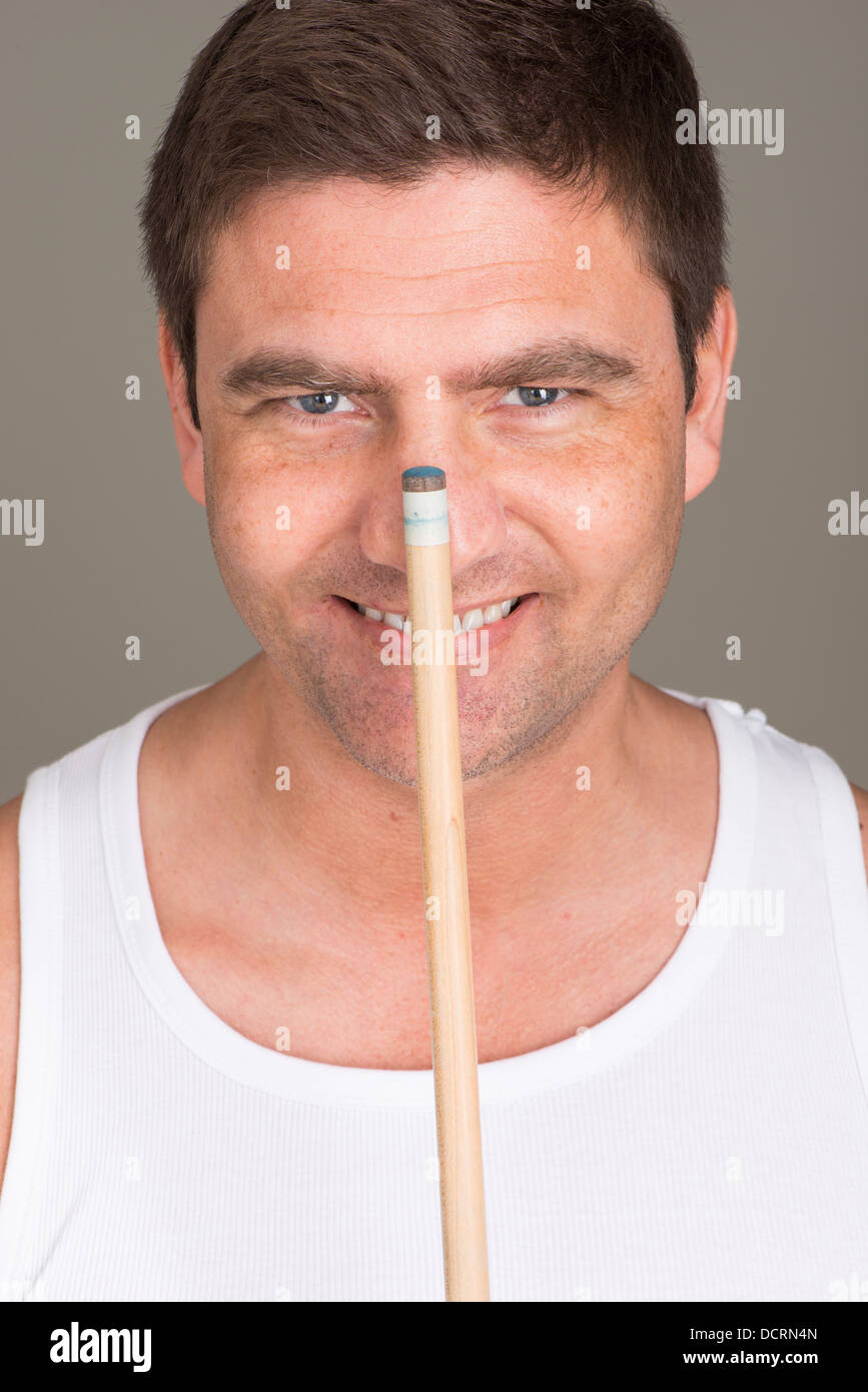 Portrait of happy adult man with billiards cue - Stock Image