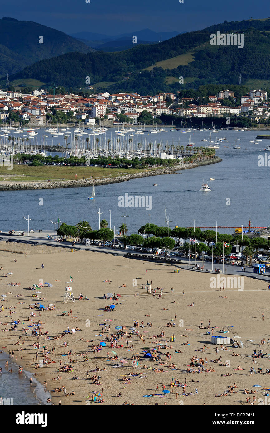 Summer on crowded Hondarribia beach in north Spain with the Bidasoa river mouth and Hendaye Beach in France in the - Stock Image