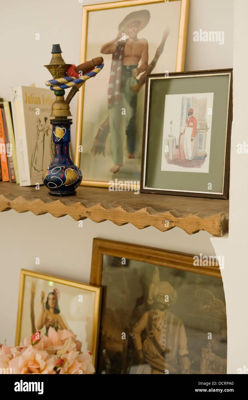 Artwork and hookah on wooden shelf - Stock Image