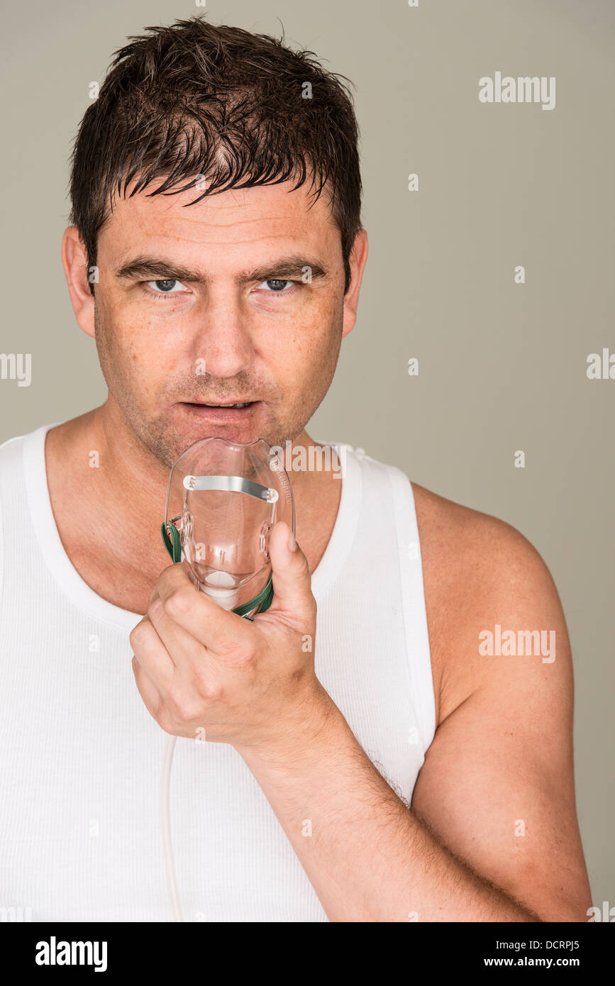 Stressed man in white tank top holding oxygen mask to help him breathe - Stock Image