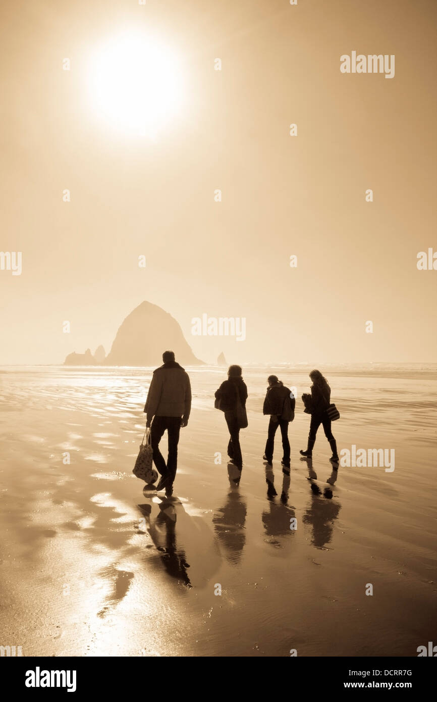 Four People Walking On The Beach; Cannon Beach, Oregon, Usa - Stock Image