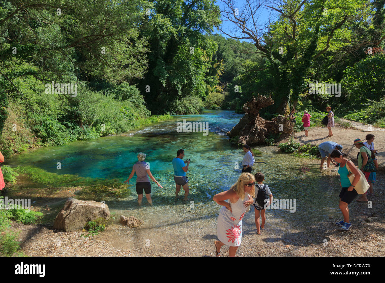 Tourists paddling in the water at the Blue Eye spring (Syri i Kalta) in southern Albania - Stock Image