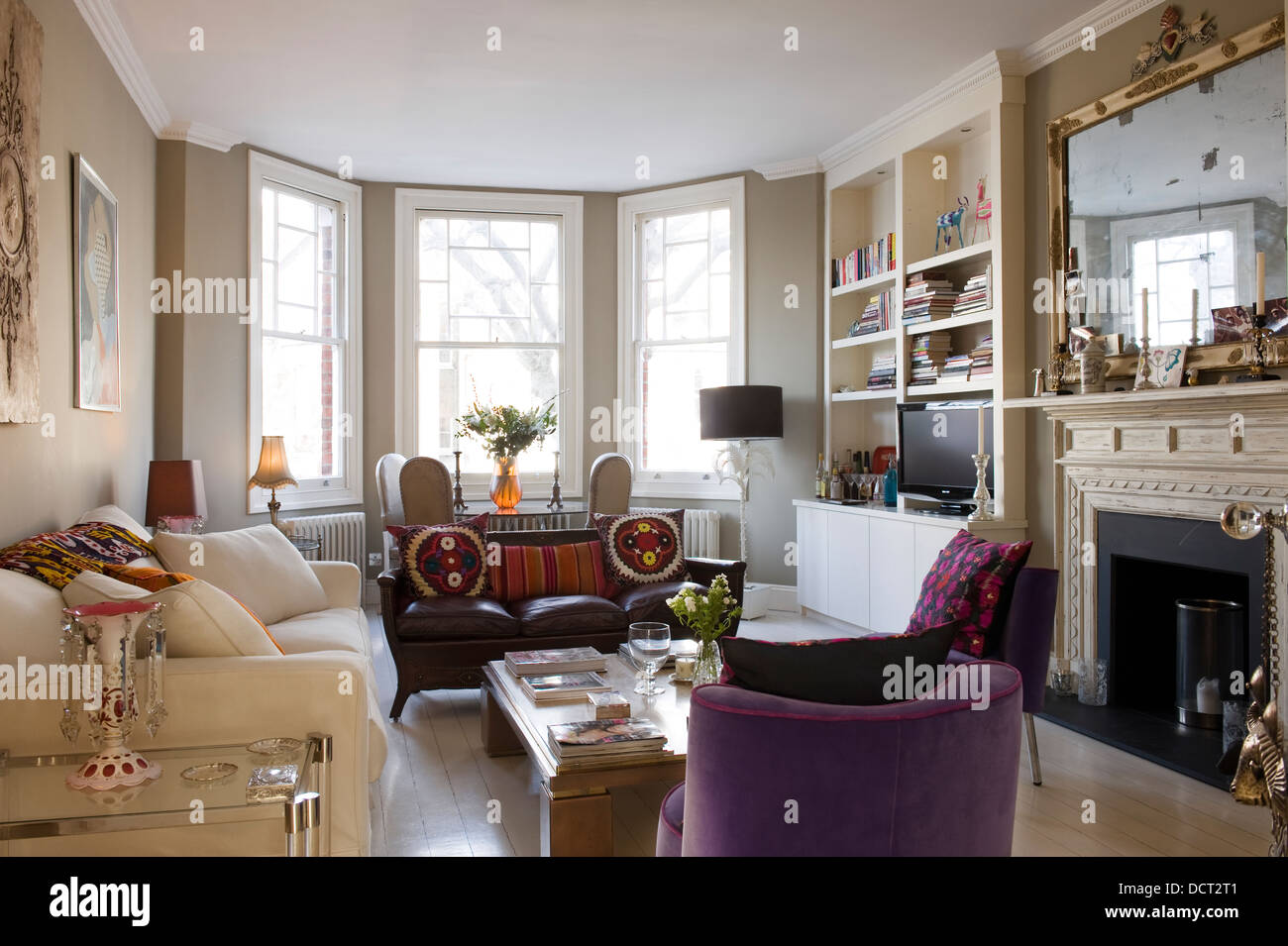 White Andrew Morton sofa in living room with assorted antique seating from Alfies Antiques Market. - Stock Image