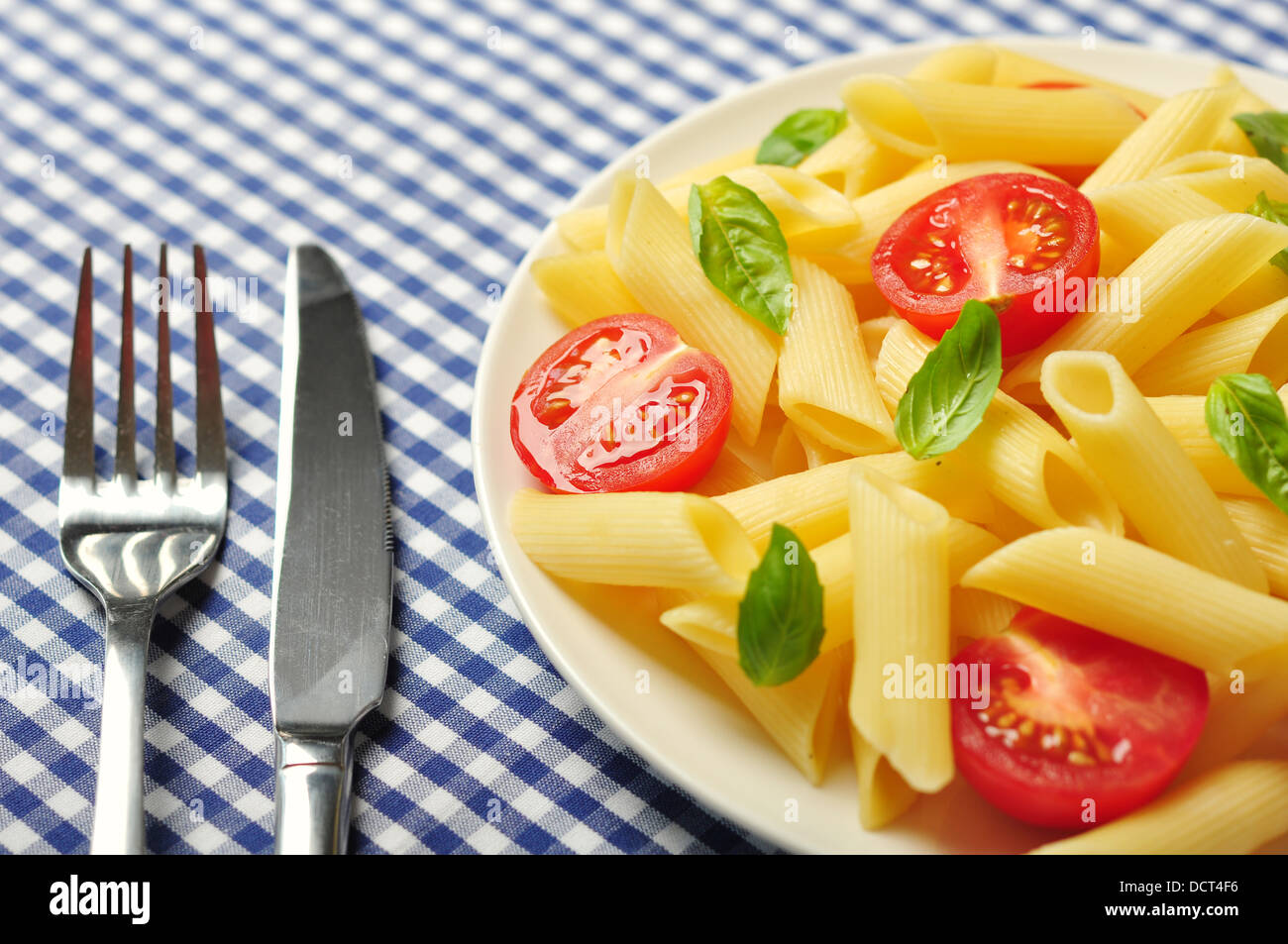 Penne pasta with cherry tomatoes and basil closeup - Stock Image