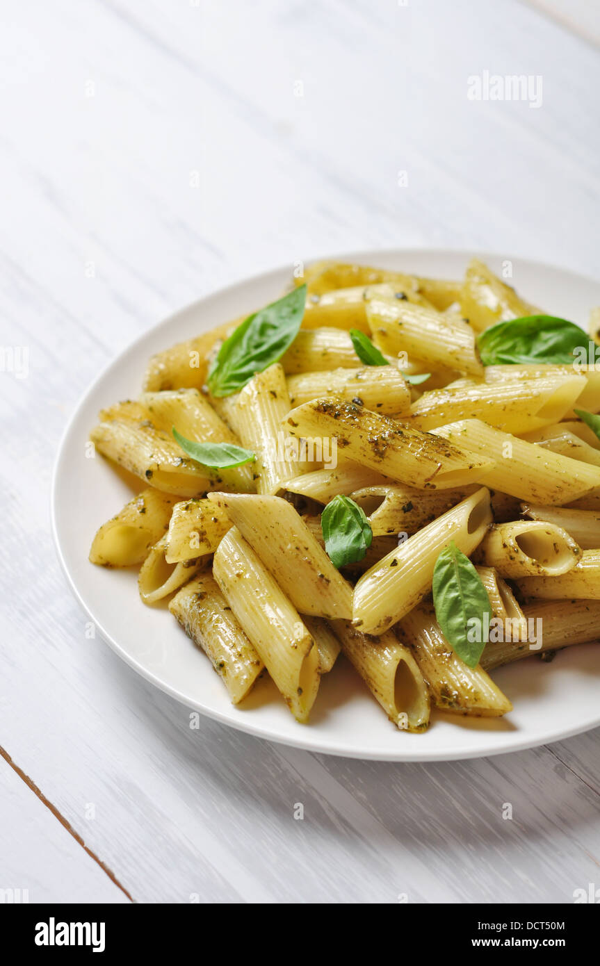 Penne pasta with pesto sauce and basil on white plate - Stock Image