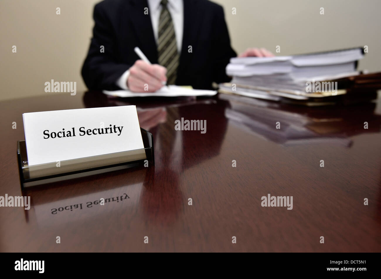 Man sitting at desk holding pen papers with business card for Social ...