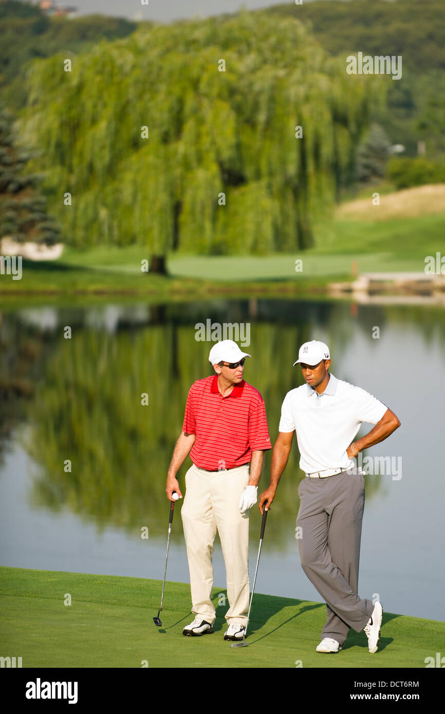 Jersey City, New Jersey, USA. 21st Aug, 2013. August 21, 2013: Tiger Woods (USA) talks to his partner in front of - Stock Image