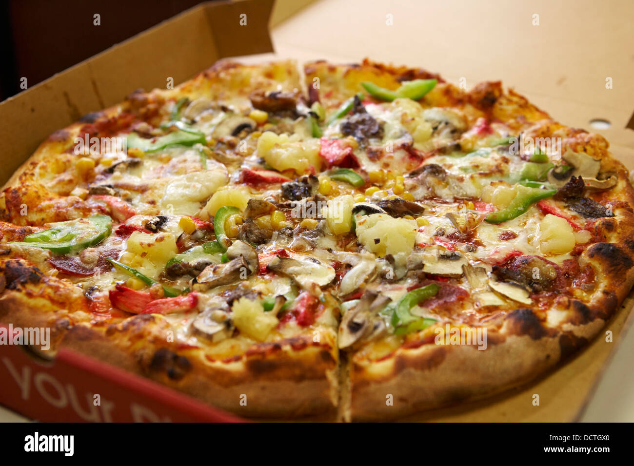 large mixed topping cheap takeaway pizza - Stock Image