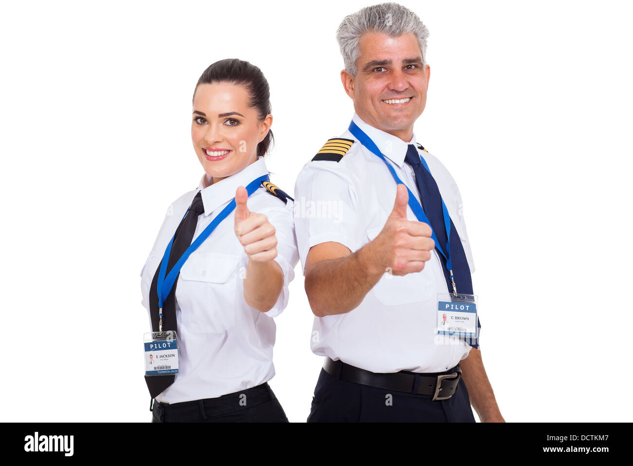 cheerful airline pilots giving thumbs up over white background - Stock Image