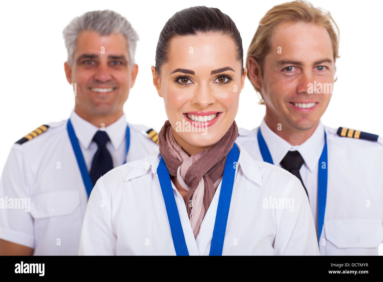 beautiful flight attendant standing in front of two pilots - Stock Image