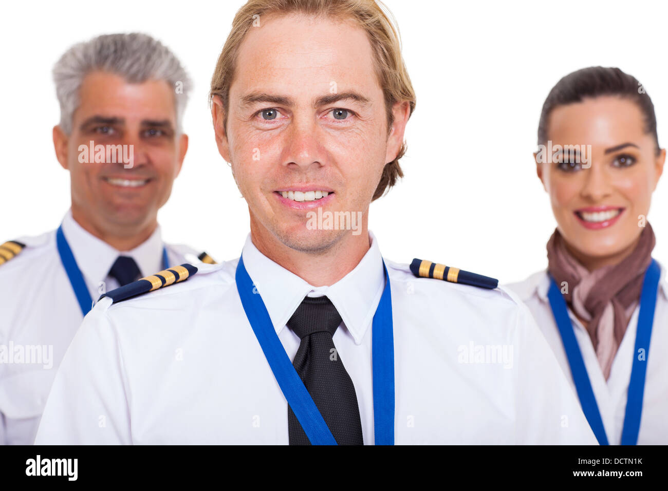 smiling first officer with airline crew over white background - Stock Image