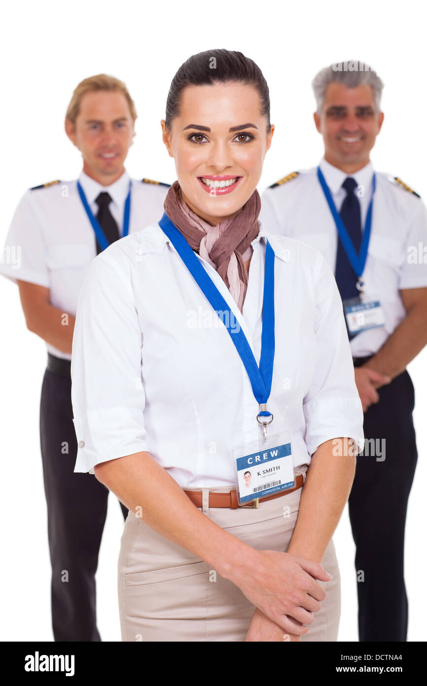 attractive airhostess standing in front of pilots on white background - Stock Image
