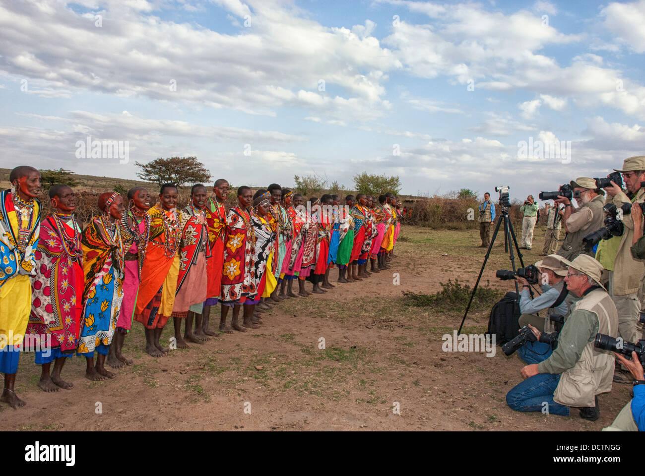 Tourist photographers taking photos of a line of Maasai women doing a welcome dance, village in Masai Mara, Kenya, - Stock Image