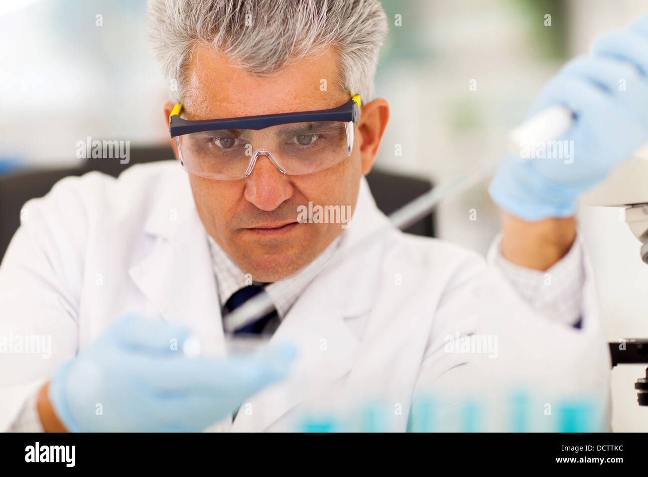 middle aged medical researcher doing microbiology experiment - Stock Image