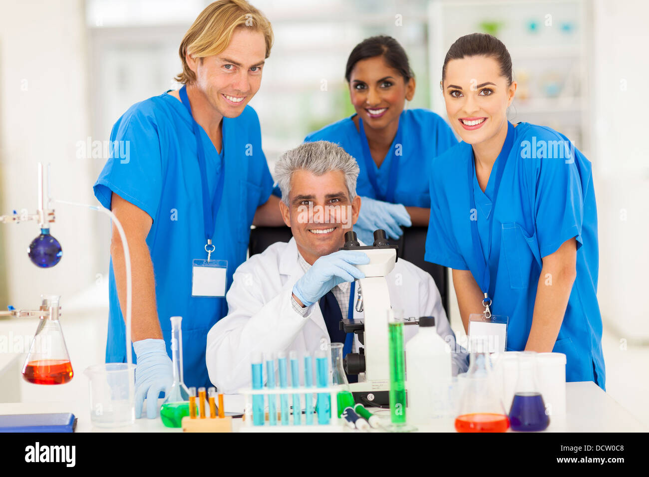 cheerful senior scientist with group of chemistry students in the lab - Stock Image