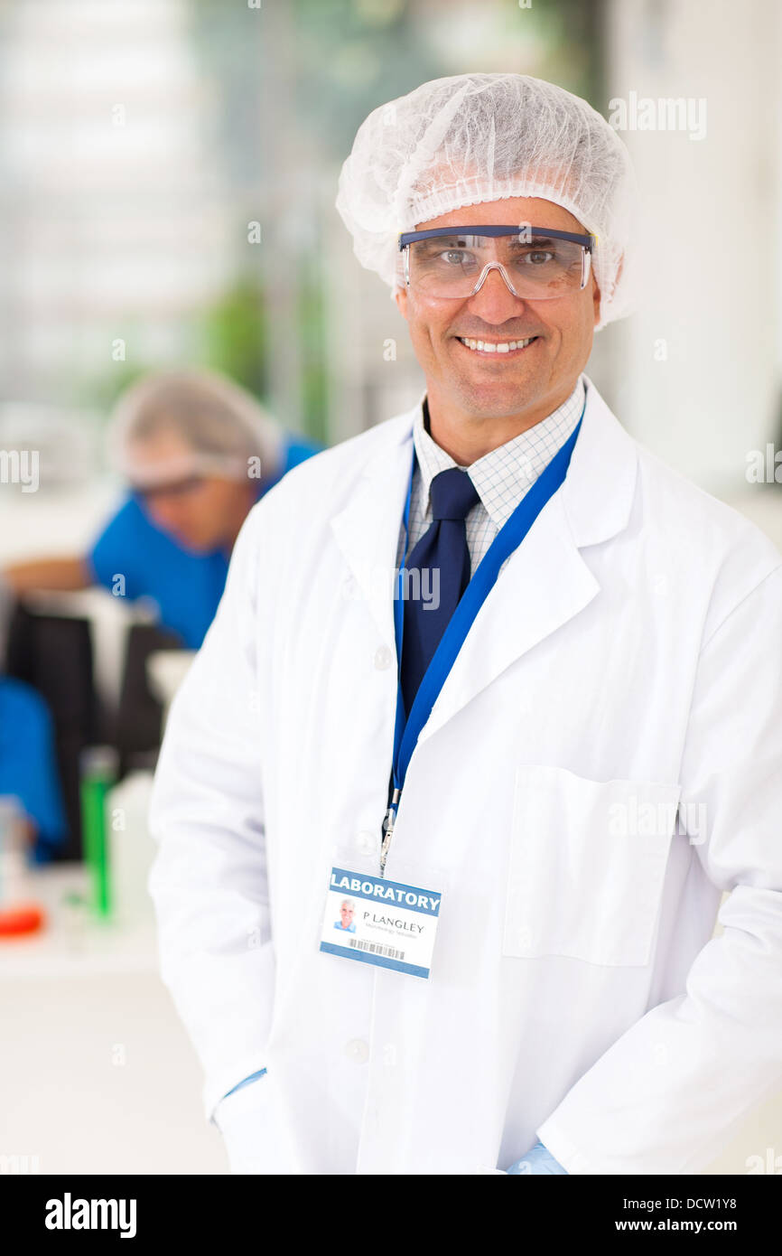 smiling senior microbiology specialist in laboratory - Stock Image