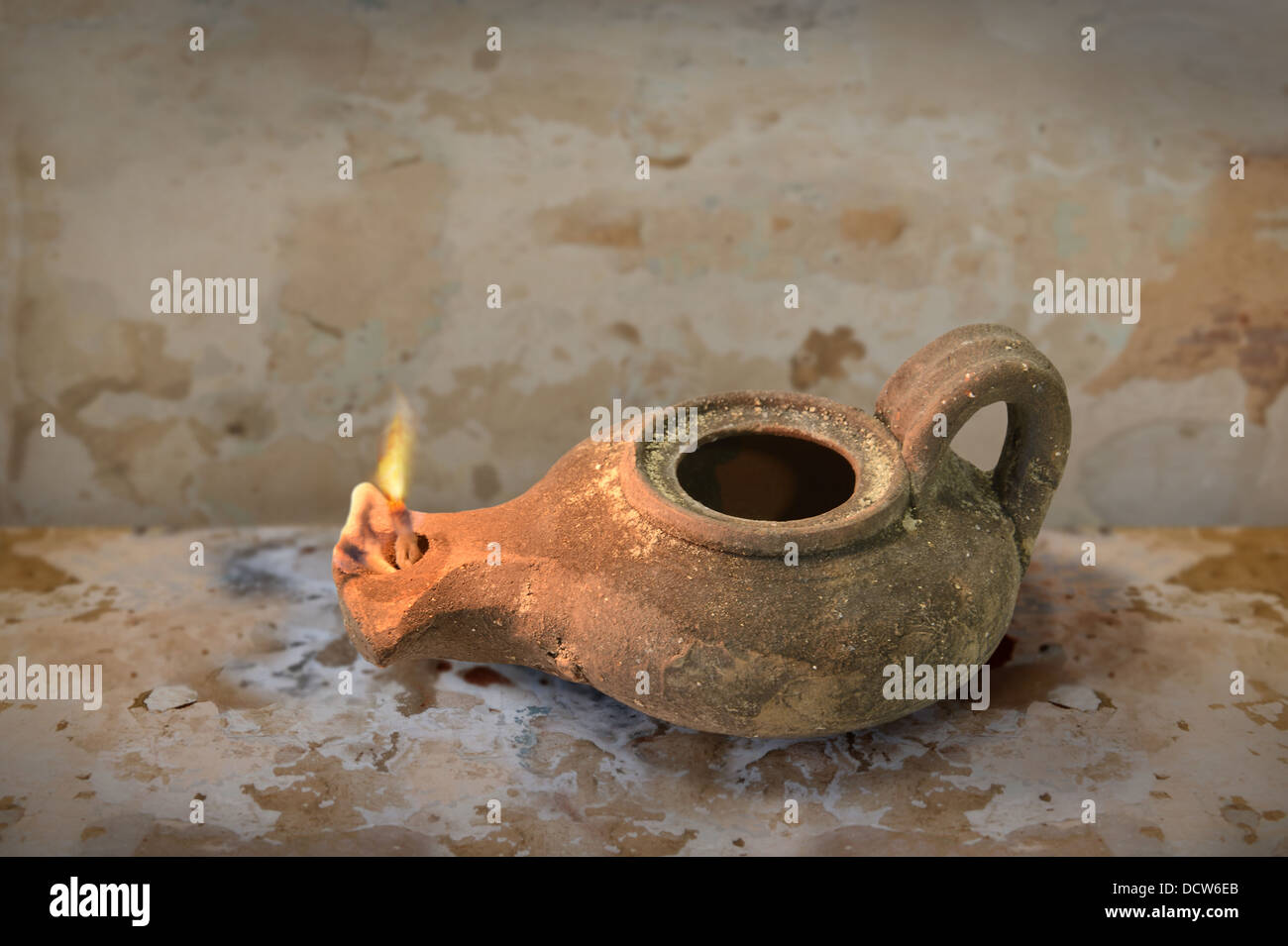 Ancient Middle Eastern oil lamp on grunge table - Stock Image