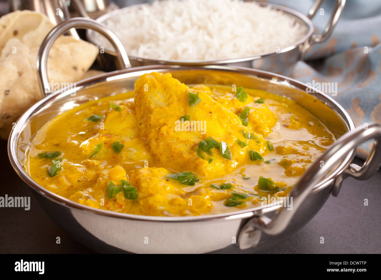 Fish Curry - a balti dish with fish curry in a yoghurt sauce with green chilli, served with poppadums. Fish is basa. - Stock Image