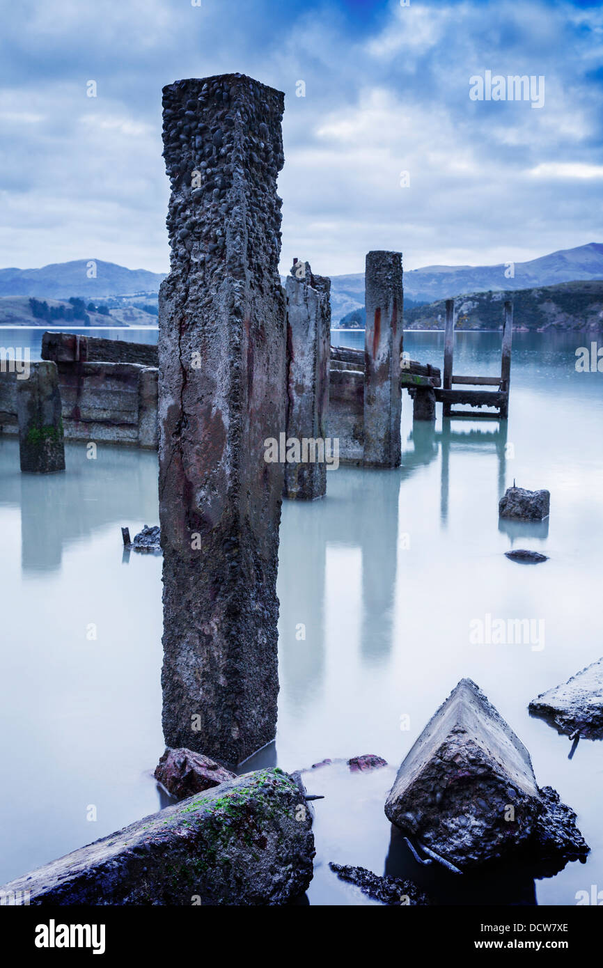 Old concrete jetty posts revealed at low water, with very smooth water, in moody light. - Stock Image