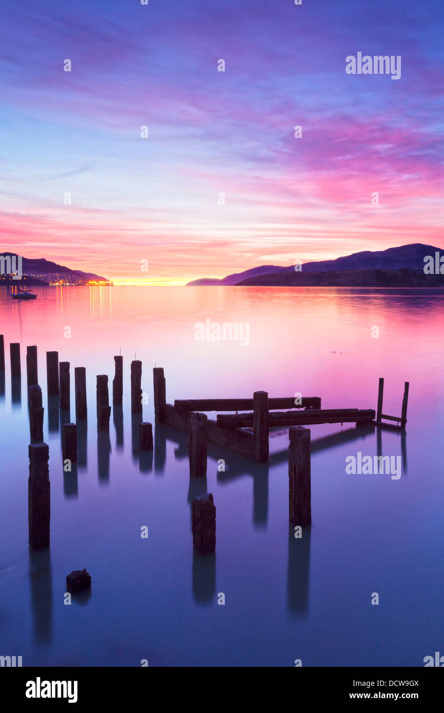 Beautiful sunrise with colours of pink, orange and purple, over Governors Bay, Canterbury New Zealand. In the foreground... Stock Photo