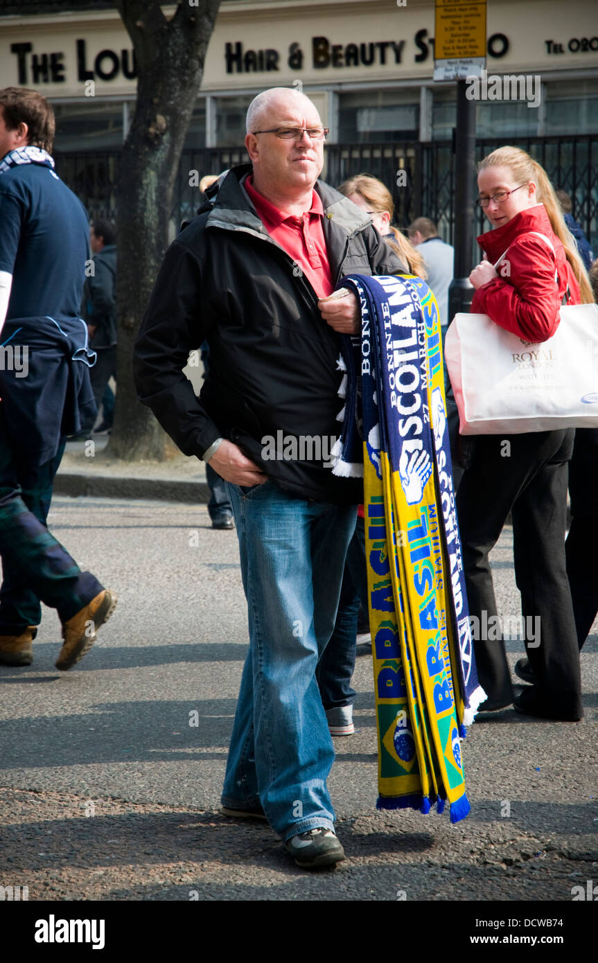 A street seller sells Brazil Scotland memorabilia before the two teams play a friendly game at Arsenal's Emirates - Stock Image