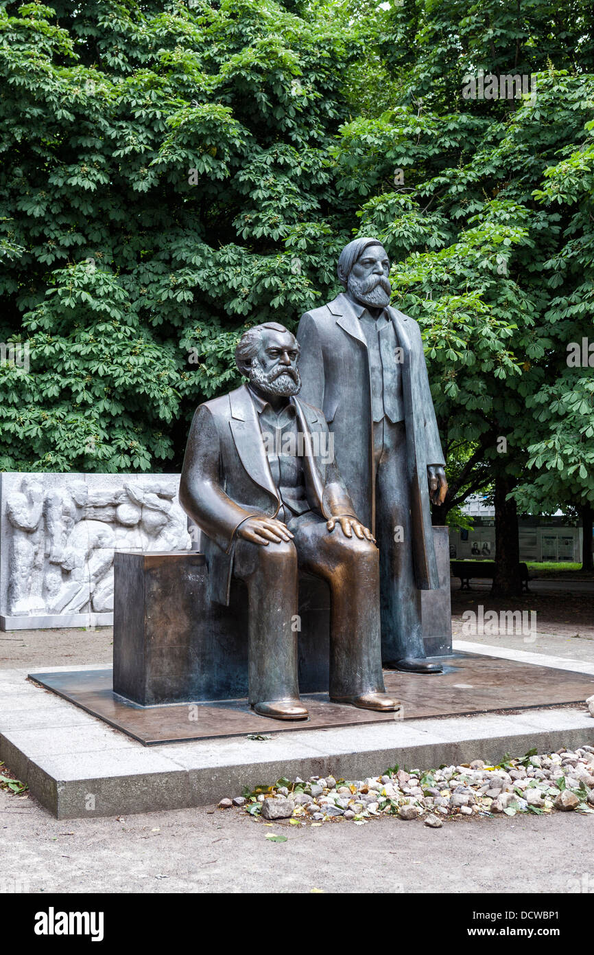 Sculpture of Karl Marx and Friedrich Engels in front of stone panel showing GDR history - Max-Engels-Forum, Berlin - Stock Image