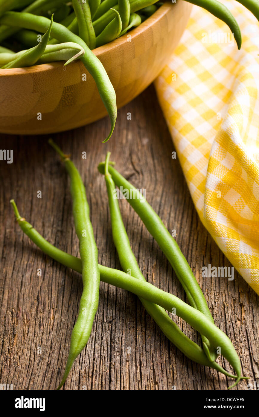 fresh green beans on old wooden table - Stock Image