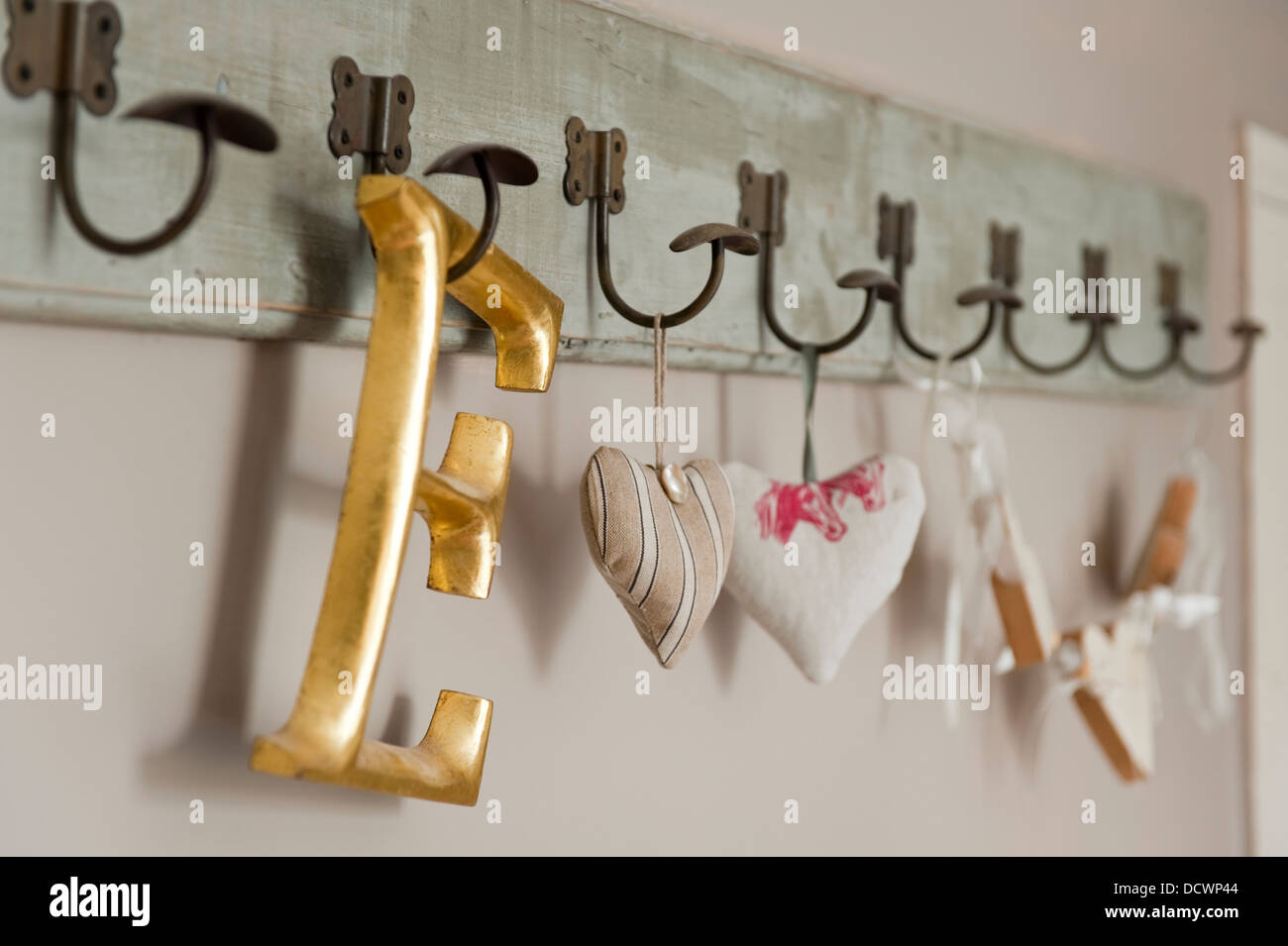 Fabric hearts and capital letter on coat hooks in Bristol home of British fabric designer Emily Bond - Stock Image