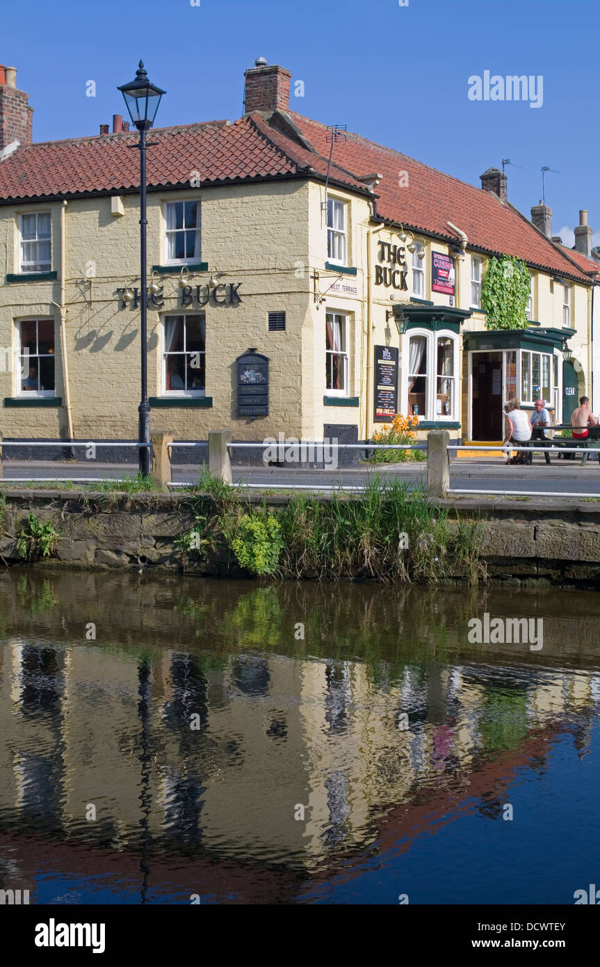 The Buck Inn Great Ayton reflected in the River Leven, hot summer afternoon, people sitting outside, North Yorkshire - Stock Image