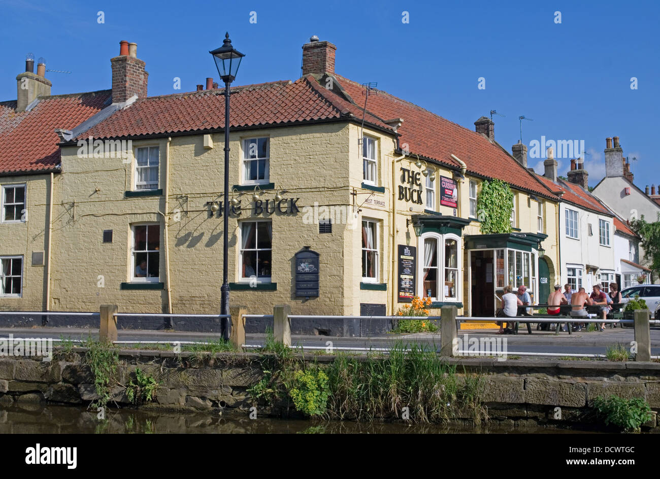 The Buck Inn, Great Ayton, by the River Leven, hot summer afternoon, people sitting outside, North Yorkshire England - Stock Image