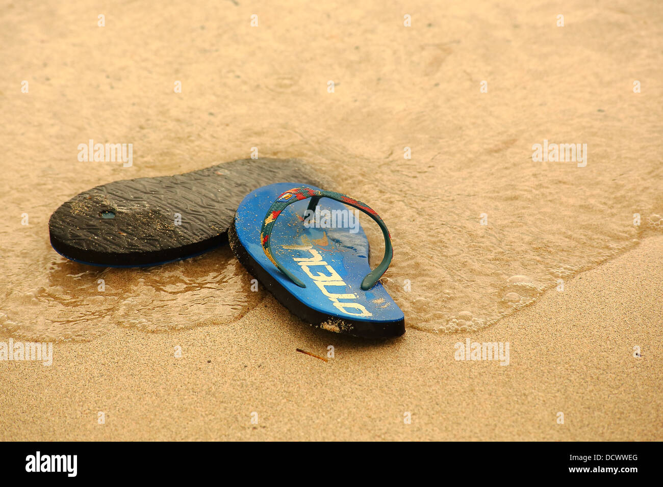 A pair of beach shoes laying discarded on a sandy beach - Stock Image