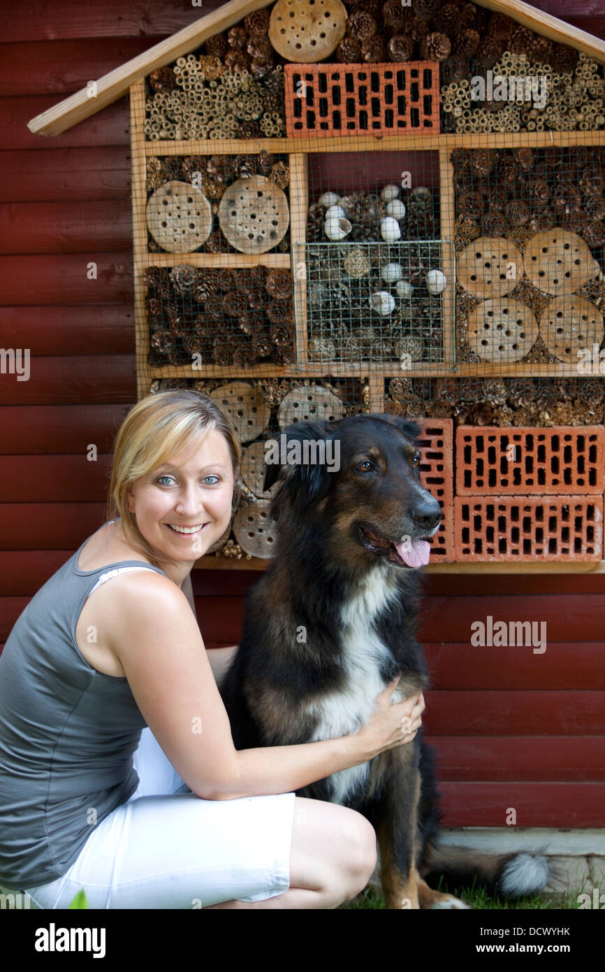 blond woman with dog showing insect hotel - Stock Image
