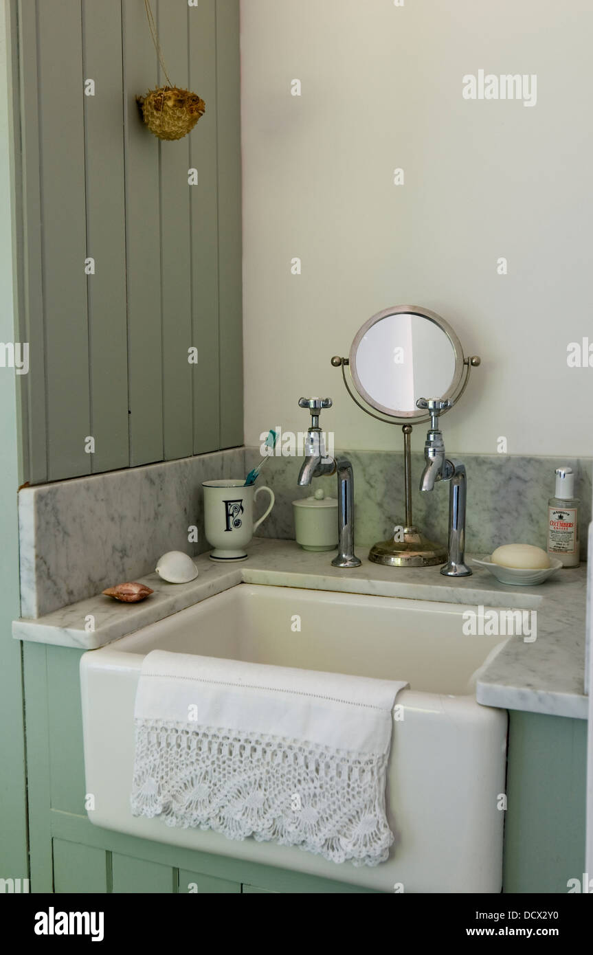 Old fashioned sink and taps in paneled bathroom with marble topped ...