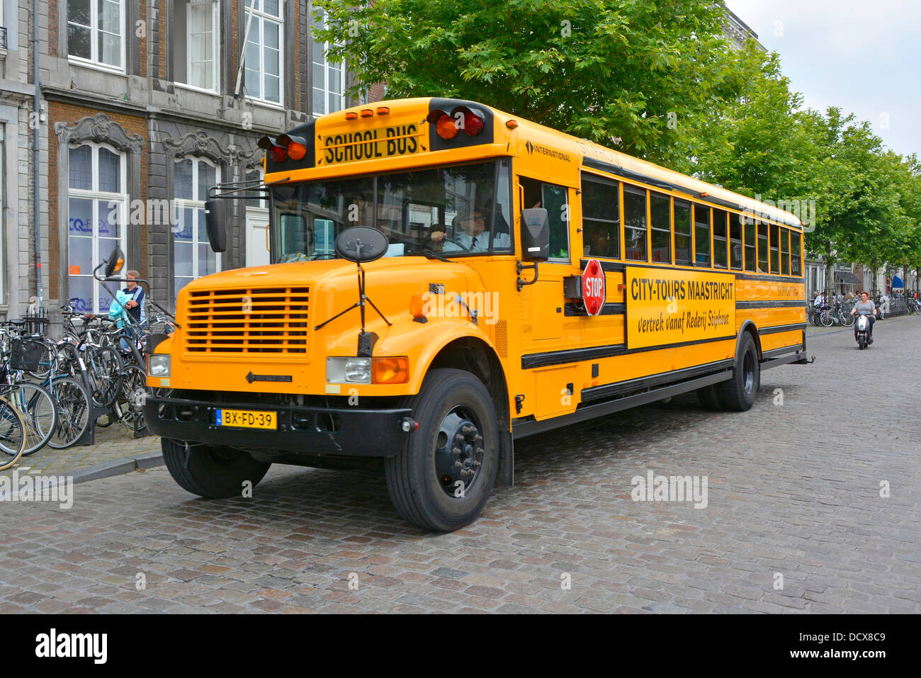 Maastricht yellow American school bus adapted for city sightseeing tours of Limburg Netherlands Europe - Stock Image